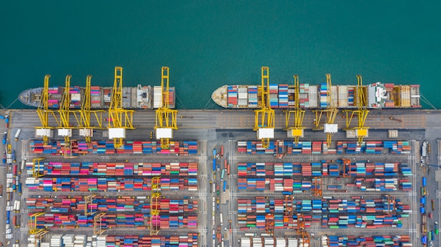 Aerial view cargo ship terminal, unloading crane of cargo ship terminal, aerial view industrial port with containers and container ship.