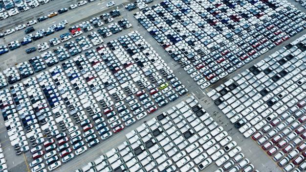 Грузовые корабли с высоты птичьего полета, перевозящие бизнес-логистику морскими перевозками, новые автомобили, произведенные год от года в порту для грузовых перевозок, и импорт-экспорт грузов по всему миру