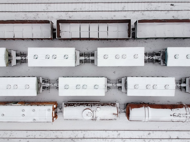 Aerial view of a cargo trains in witer . freight trains covered with snow on the railway station. heavy industry. no people.