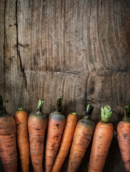 Aerial view of carrots on wooden background