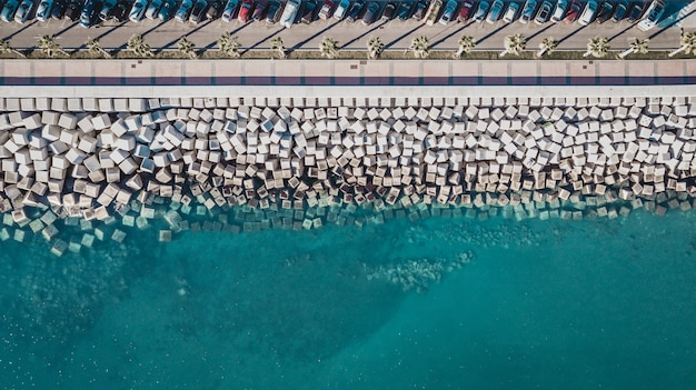 Aerial view of cement cube blocks protecting the shore from the waves in the port in malaga