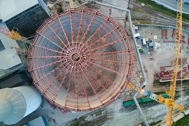 Aerial view of cement factory under construction with high concrete plant structure and tower cranes at industrial production area. manufacture and global industry concept.