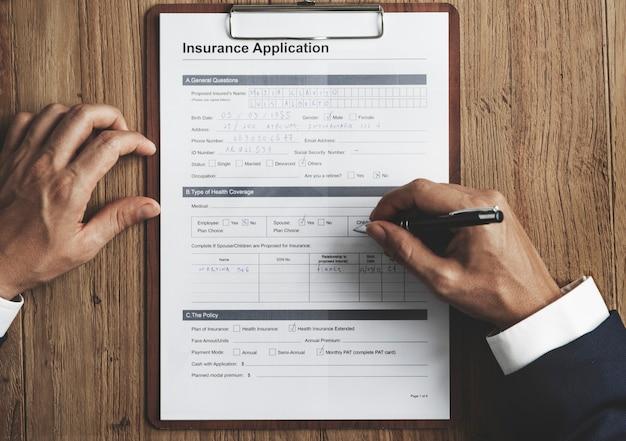 木製のテーブルの上の保険申請書に記入する手の空中写真のクローズアップ