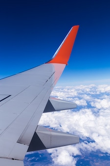 Aerial view of cloud blue sky and plane wing view through the airplane window.