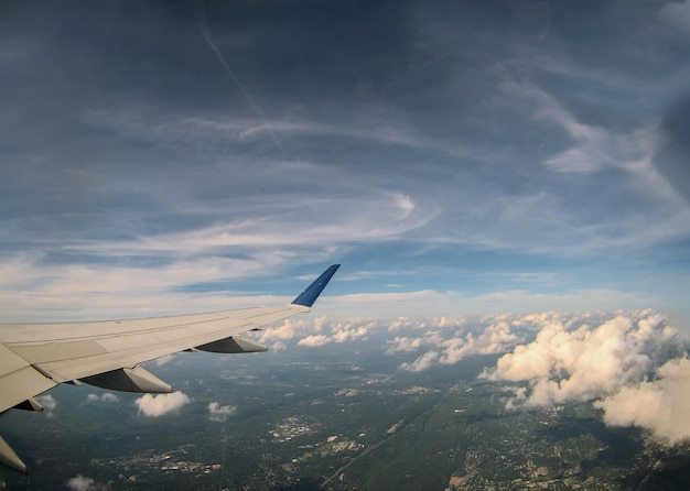Aerial view on of cloud and sky with airplane wing from window