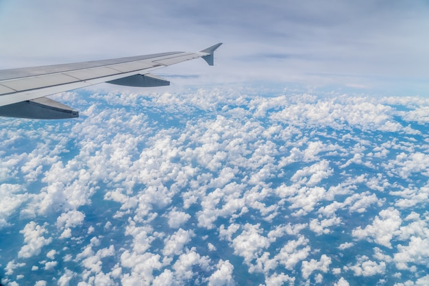 Aerial view above clouds from airplane window with blue sky.  tropical climate in thailand.