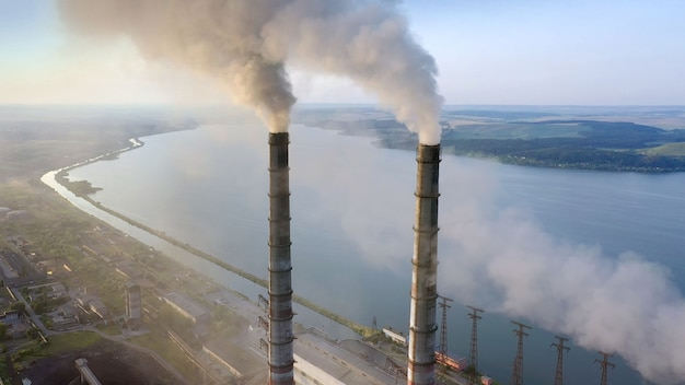 Aerial view of coal power plant high pipes with black smoke moving up polluting atmosphere at sunrise.