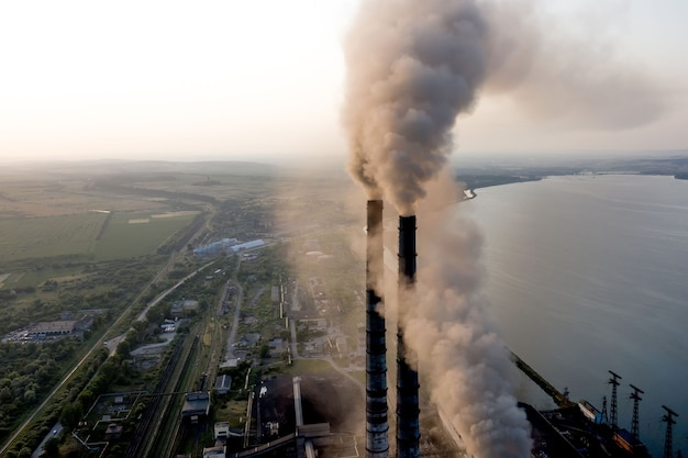 Aerial view of coal power plant high pipes with black smoke moving up polluting atmosphere at sunset.