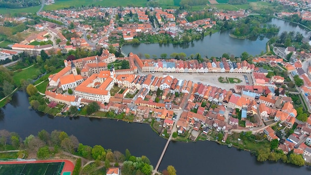 Aerial view of colorful buildings with red tile roofs at the medieval square and old castle in telc, czech republic