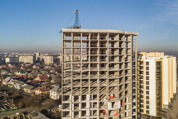 Aerial view of concrete frame of tall apartment building under construction in a city.