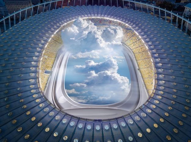 夜間のサッカー場の代わりに、照明窓と曇った青い空を備えたスタジアムの空中写真の建設。旅行と輸送の概念。