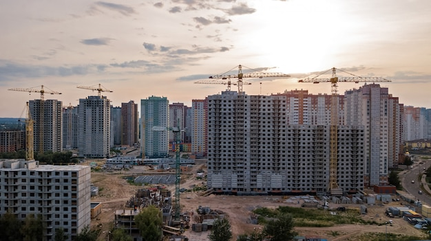 Aerial view of construction site of residential area buildings with cranes at sunset