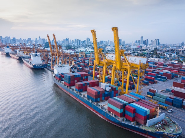 Aerial view of container ship loading containers by working crane in port terminal with container shipyard and imports exports logistics