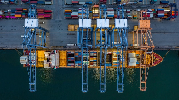 Aerial view container ship loading at night in industrial port.