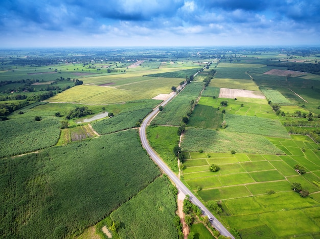 Aerial view of a country road amid fields with a white car