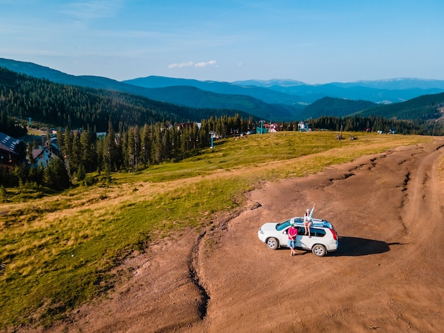 Aerial view of couple sitting on the suv car roof enjoying view of carpathian mountains ukraine