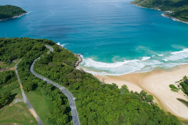 Aerial view of curve road along the naiharn beach at phuket thailand beautiful sandy beach and open sea in summer season nature recovered environment and travel background.