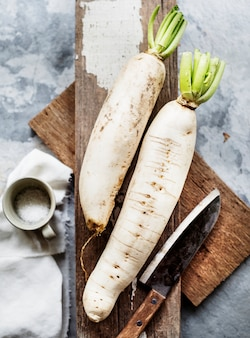 Aerial view of daikon radish on wooden cutboard with knife