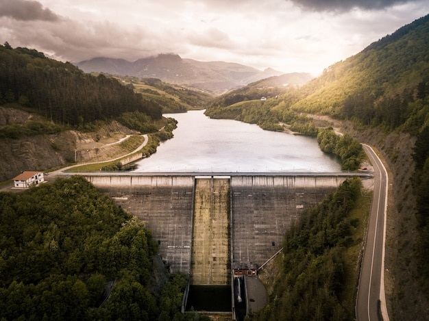 Aerial view of a dam at sunset on a cloudy day in the middle of a mountainous forest. dam on a mountain river with a road