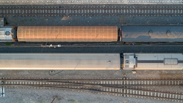 Aerial view of diesel locomotive train and railway tracks - top view pov of industrial conceptual scene with trains