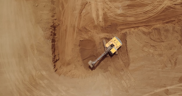 Aerial view of a digger, tracked excavator at work on a construction.