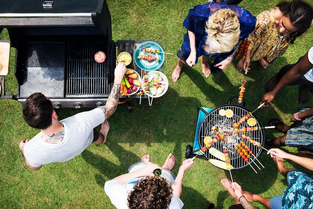 Aerial view of diverse friends grilling barbecue outdoors
