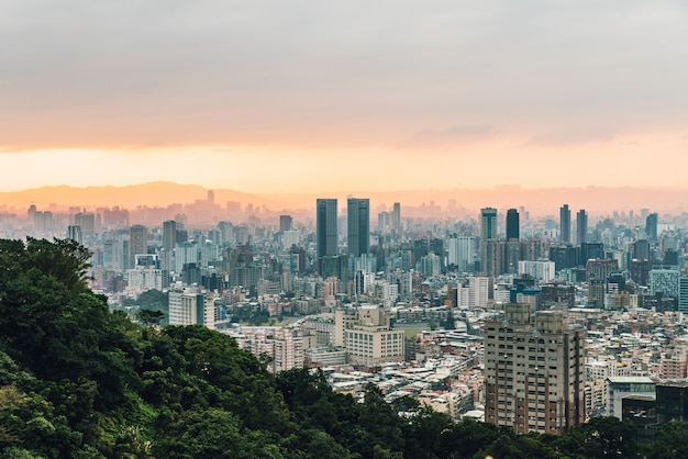 Aerial view over downtown taipei with layers of mountain in background in the dusk from xiangshan elephant mountain in the evening.