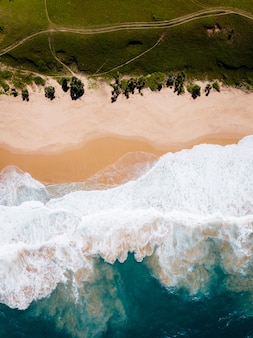 Aerial view drone camera of tropical sea and wave crashing on sandy shore