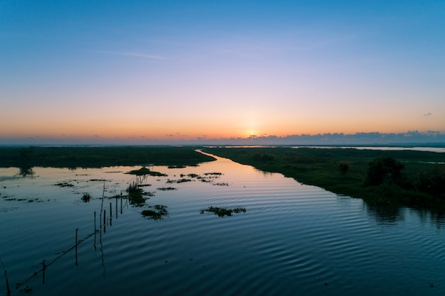 Aerial view drone shot of beautiful scenery sunlight in the morning sunrise above lake in phatthalung thailand