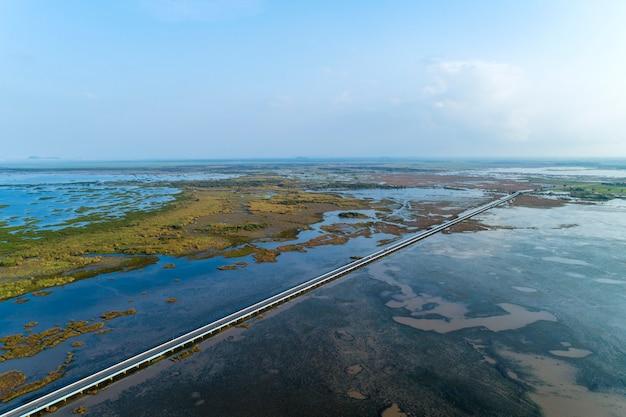 Aerial view drone shot of bridge (ekachai bridge). colorful road bridge cross the lake at talay noi lake in phatthalung province thailand