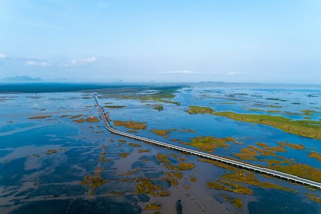 Aerial view drone shot of bridge(ekachai bridge)colorful road bridge cross the lake at talay noi lake in phatthalung province thailand
