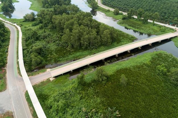 Вид с воздуха с дронов на дорогу между зеленым полем летнего леса и рекой и озером