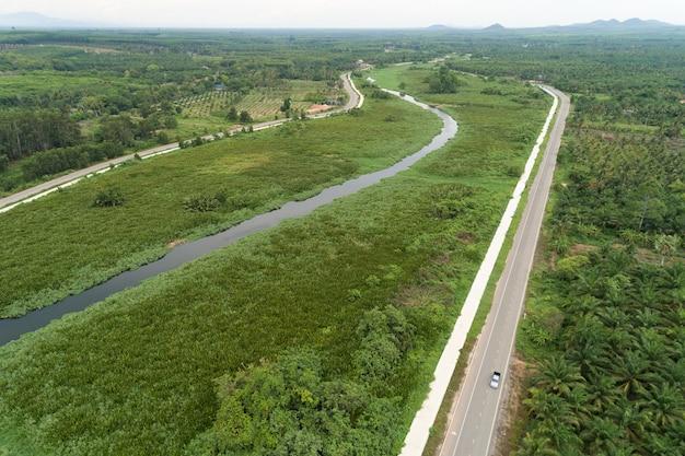 Вид с воздуха с дронов на дорогу между зеленым полем, летним лесом и рекой и озером