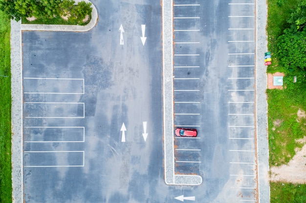 Aerial view drone top down of parking lot with cars and arrow sign on road