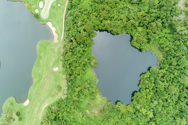 Aerial view drone top down shot of beautiful green golf field high angle view in summer time