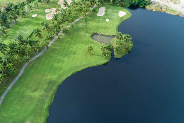 Aerial view drone top down shot of beautiful green golf field and palm trees high angle view in summer time Premium Photo