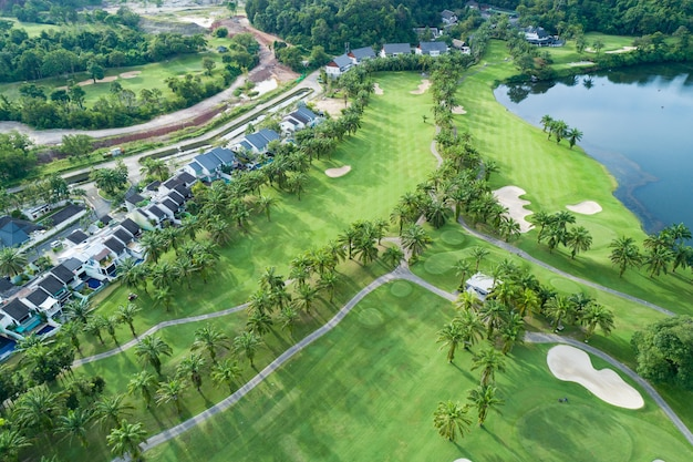 Aerial view drone top down shot of beautiful green golf field with modern villa