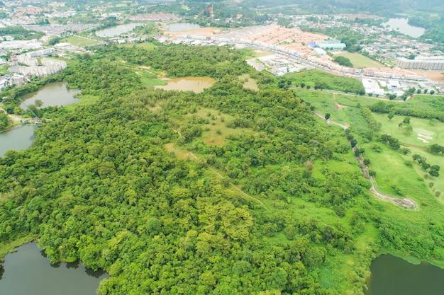 공중 보기 드론 여름 시간에 도시가 숲을 둘러싸고 있는 풍부한 숲의 하향식 높은 각도 보기 자연 환경 개념입니다.