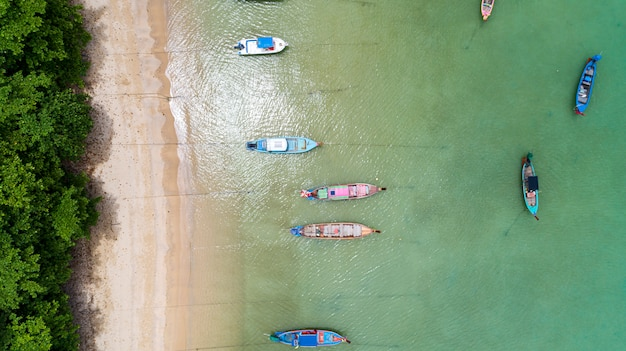 Aerial view drone top down of thai traditional longtail fishing boats in the tropical sea beautiful beach