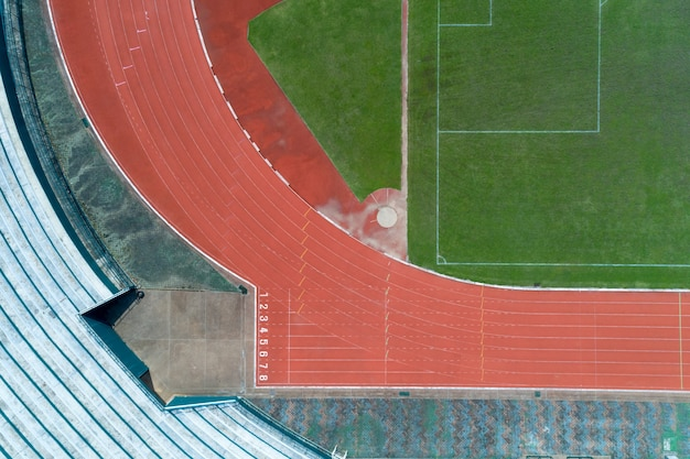 Aerial view of empty green football field with running track, running track with number in top view.