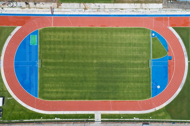 Aerial view of empty new soccer field from above with running tracks around it amazing new small stadium for many sport disciplines at phuket thailand.
