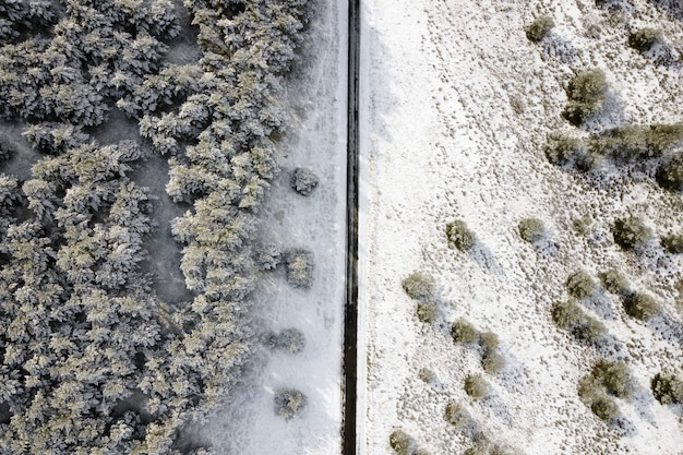 Aerial view of empty snow covered road in winter forest..