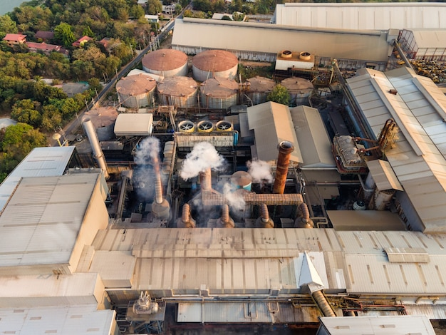 Aerial view of ethanol industrial or biofuel refinery processing factory with smoke from chimney, storage tanks and warehouse