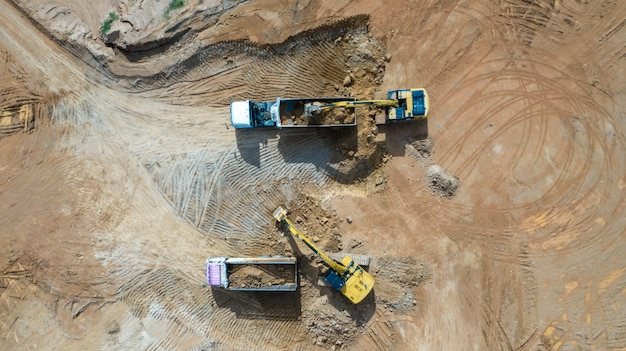 Aerial view excavators and trucks working at construction site