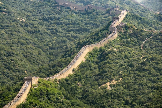 Aerial view of the famous great wall of china surrounded by green trees in summer