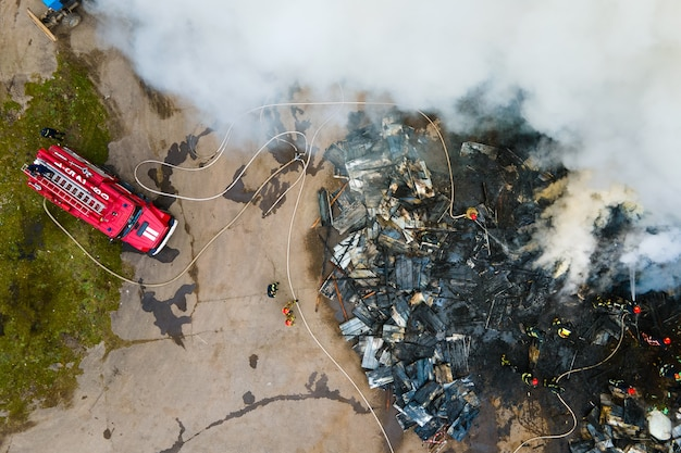 Aerial view of firefighters extinguishing fire in industrial area.