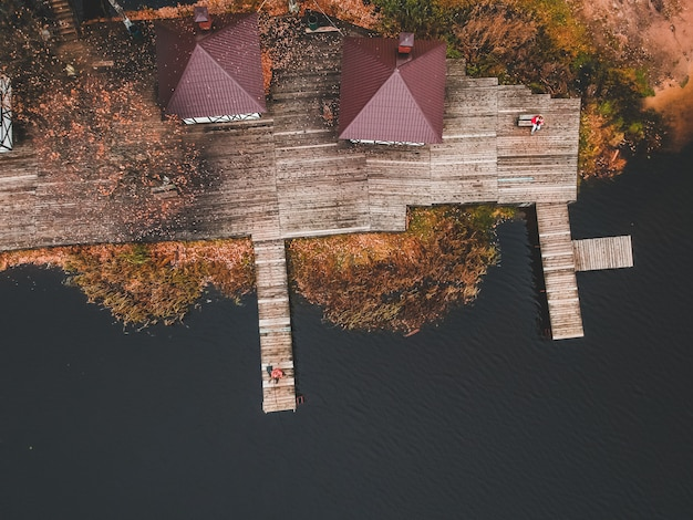 Aerial view of a fisherman with a fishing rod on the pier, lake shore, autumn forest. finland.