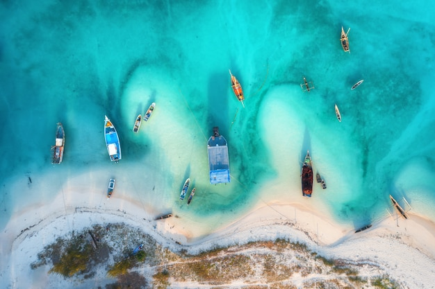 Aerial view of the fishing boats in clear azure water at sunset in summer