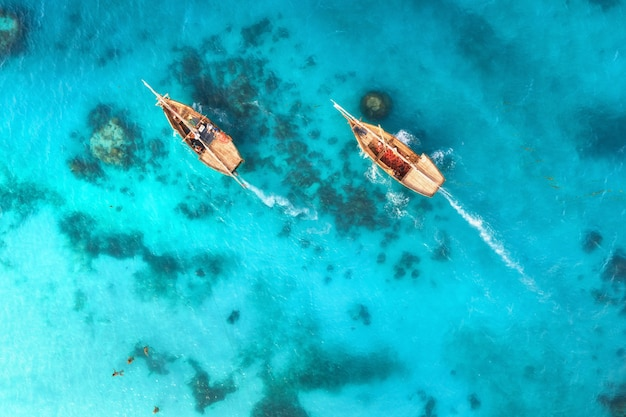 Aerial view of the fishing boats in clear blue water at sunset in summer