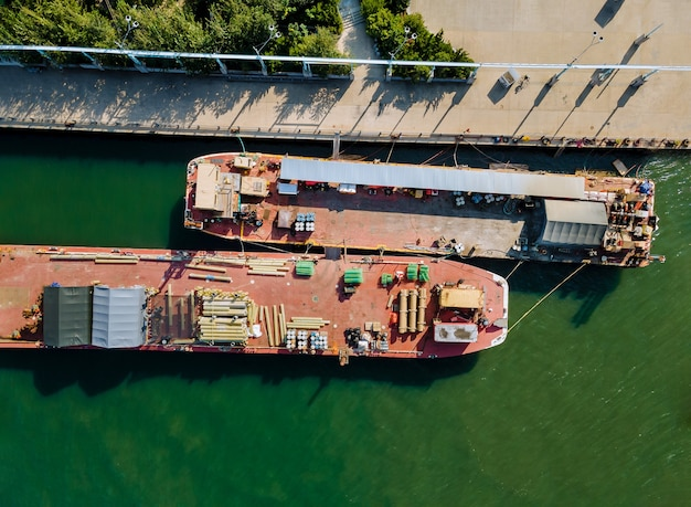 Aerial view of floating cargo transportation by construction materials transported building pipes and metal structures on barges